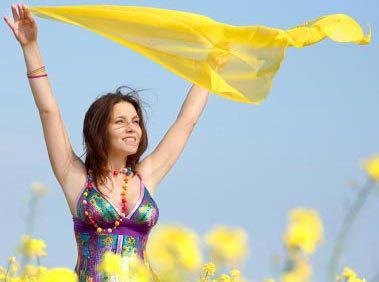 Confident woman standing in a field due to hypnosis for confidence